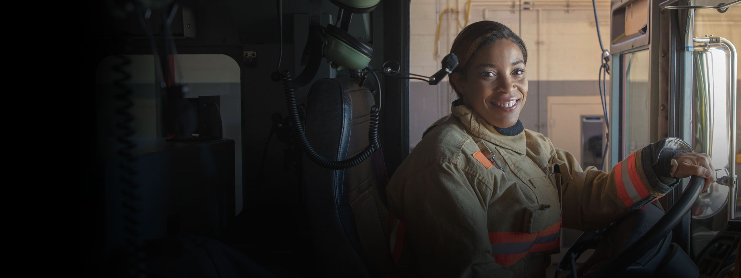 Firefighter smiles as she sits in the fire engine cab with her hand on the wheel.