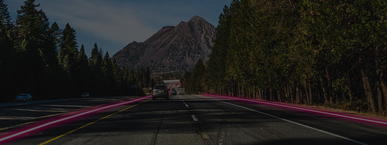 Rural interstate highway with mountains, trees, and a swath of magenta lights.