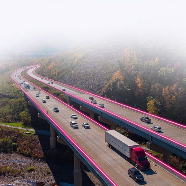 Rural interstate highway from driver's point of view with T-Mobile magenta highlights.