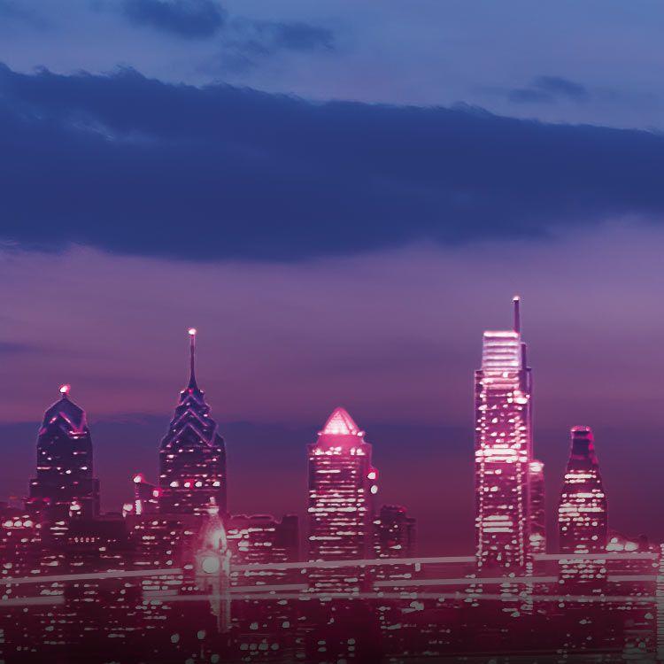 Philadelphia skyline lit up with magenta beams and lights