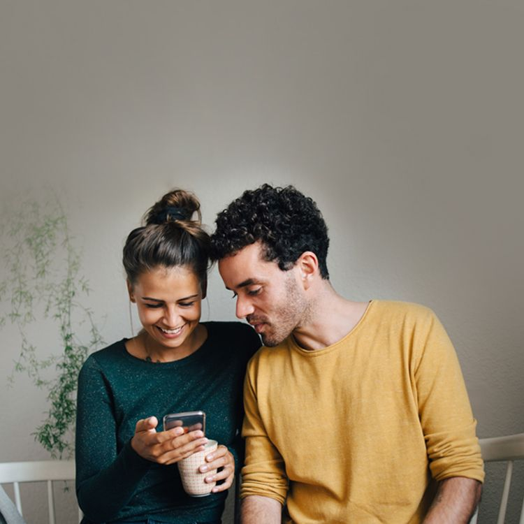 Man looking at woman's phone while sitting at a table