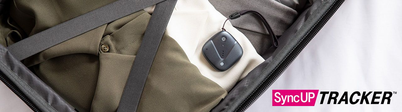 Sync-up tracker device resting on clothes packed in suitcase.