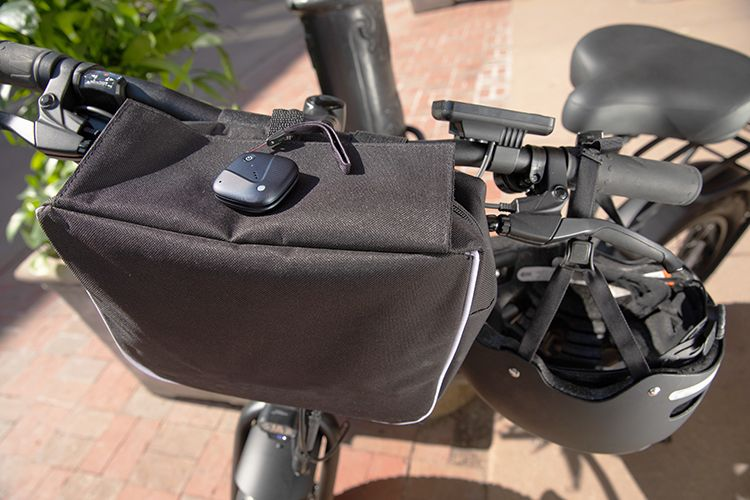 Sync-up tracker attached to black bag wrapped around bicycle handlebars.