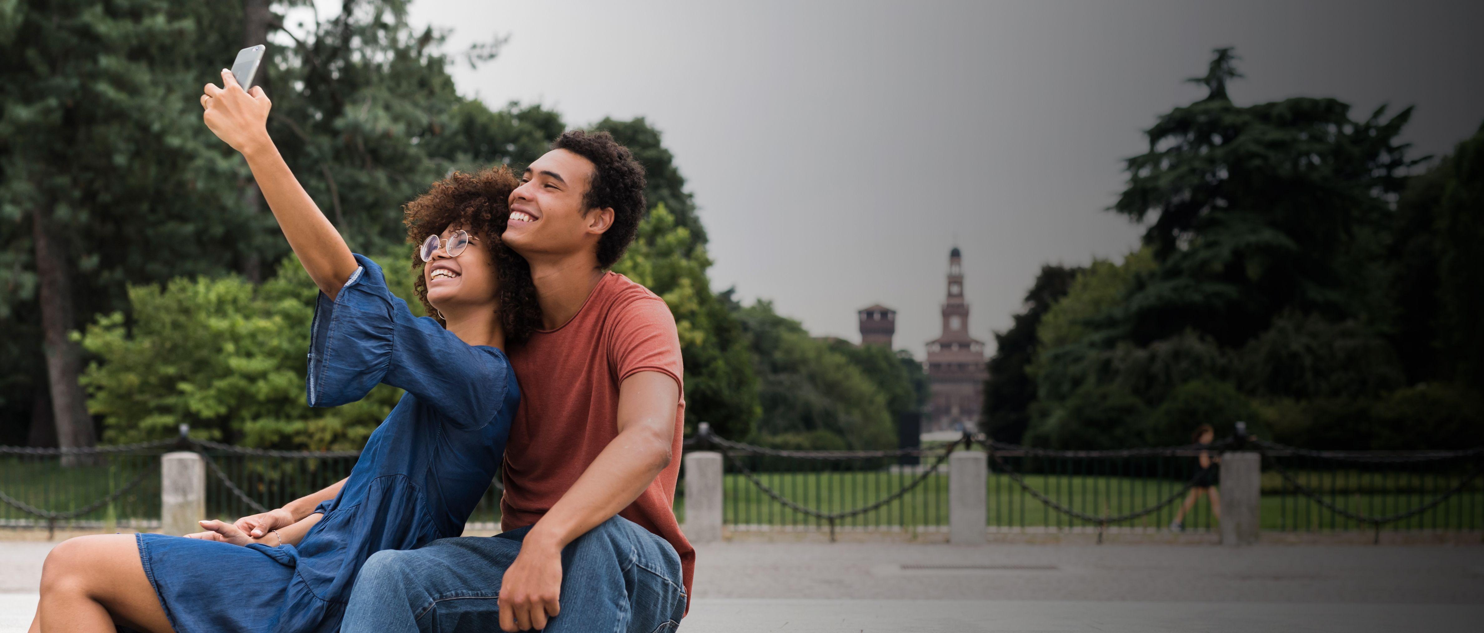 Hombre y mujer sonriendo y tomándose un selfie en exteriores