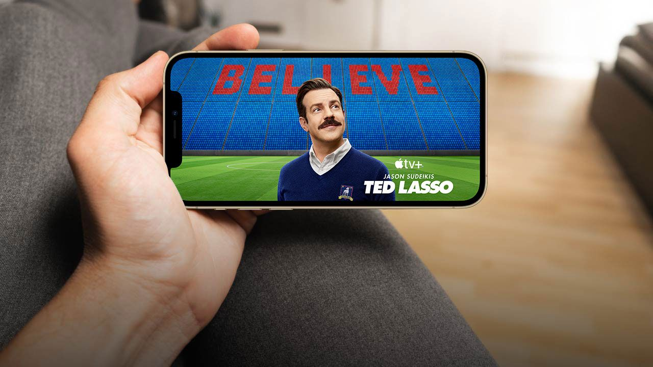 Hand holding an iPhone. In the iPhone screen is Jason Sudeikis as Ted Lasso.