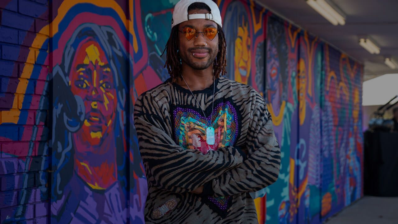 Artist standing in front of a mural he created.