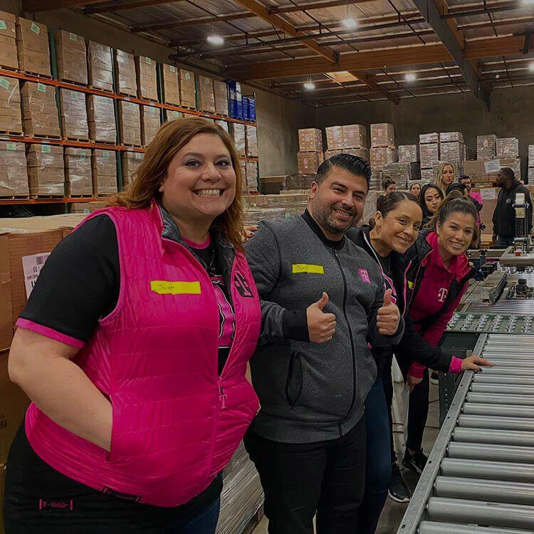 Empleados de T-Mobile sonriendo en un depósito.