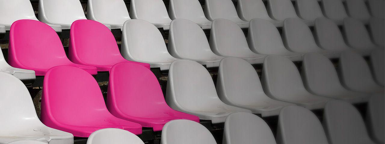 Magenta stadium seats amid grey stadium seats