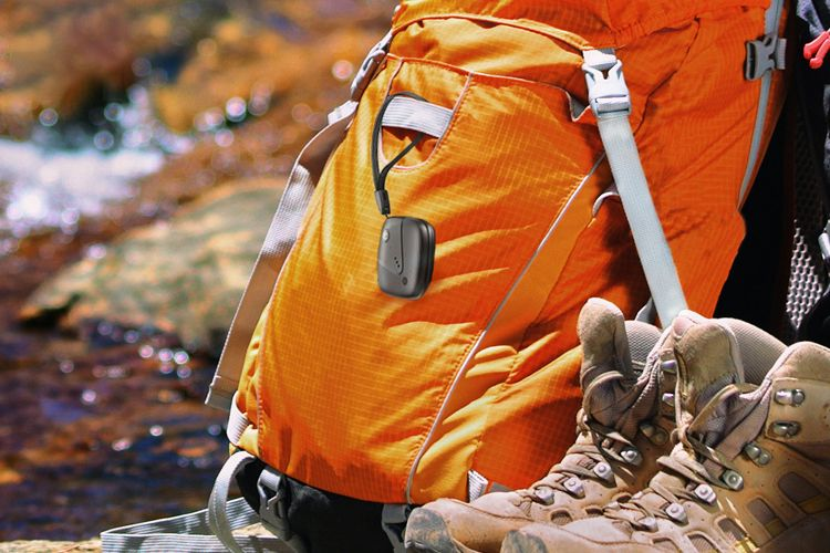 Sync-up tracker attached to backpack resting near hiking boots and stream.