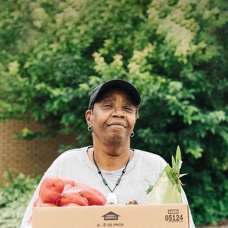 A woman holding a box of vegetables and smiling.