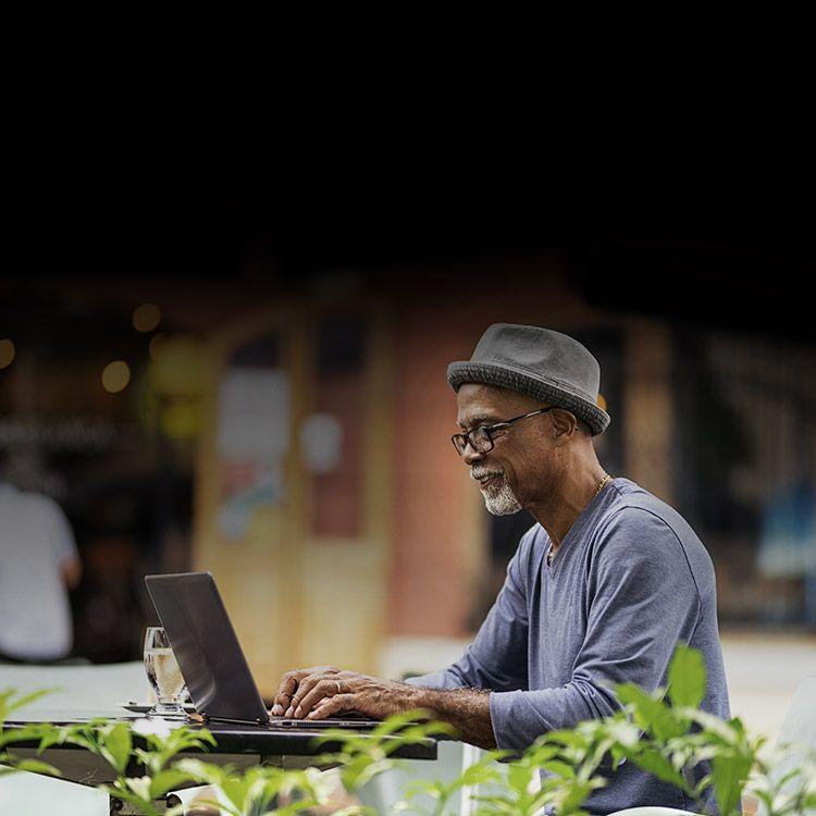 Hombre mirando su laptop sentado en una cafetería