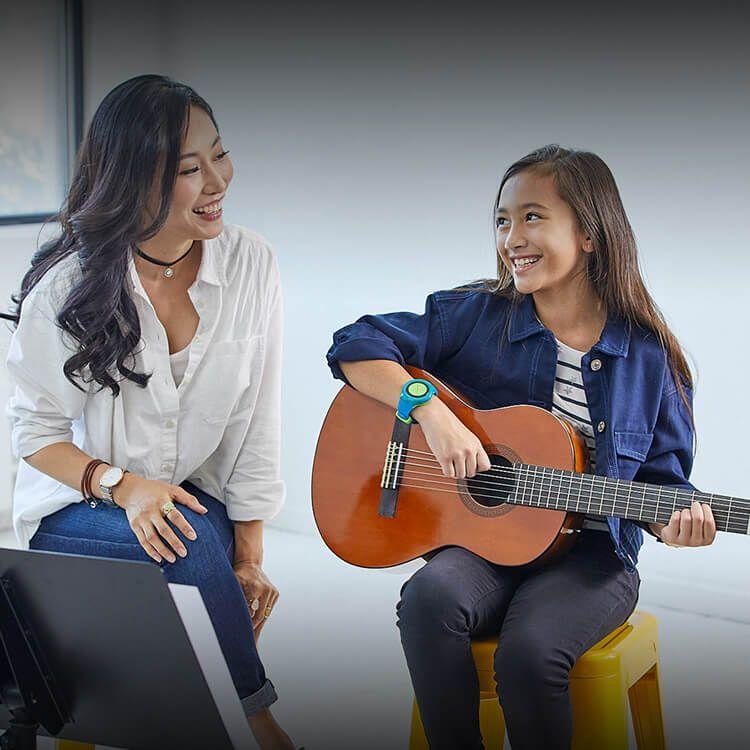 Una niña usando un reloj TIMEX Family Connect y tocando la guitara sonríe a una mujer que está junto a ella.