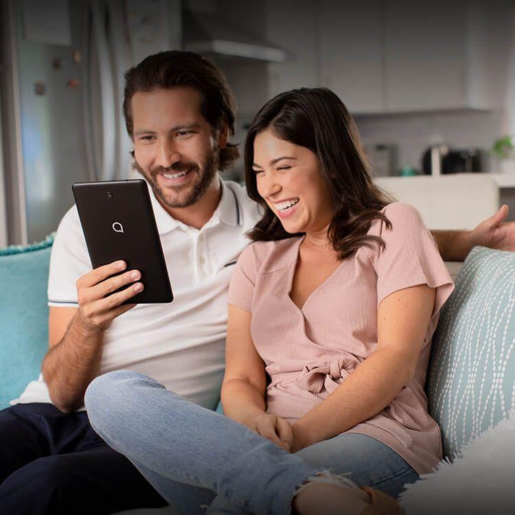 Un hombre y una mujer sentados en un sofá sonríen ante una alcatel JOY TAB.