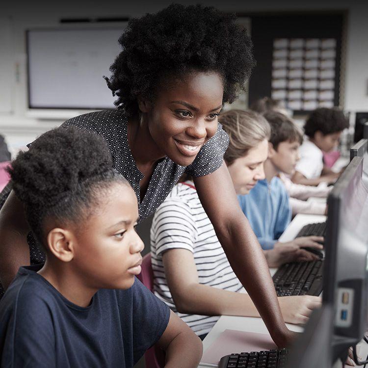 Una niña y su maestra miran la pantalla de una computadora.