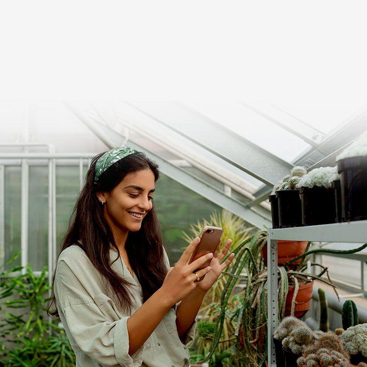 Mujer mirando su teléfono parada en un invernadero
